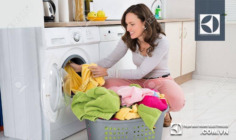Mở cửa và cho quần áo vào lồng giặt